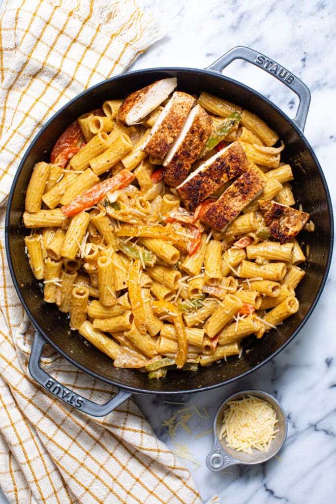 Rasta Pasta with chicken in gray skillet on marble surface