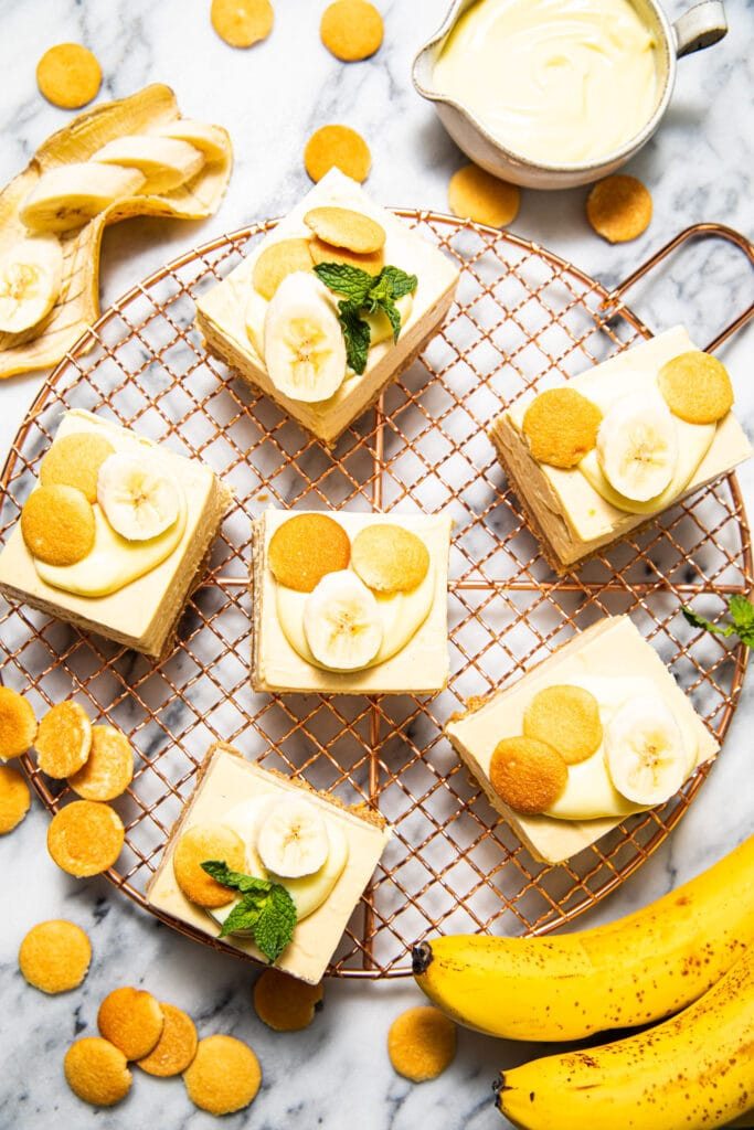 banana pudding cheesecake bars on copper wire rack with bananas on the side
