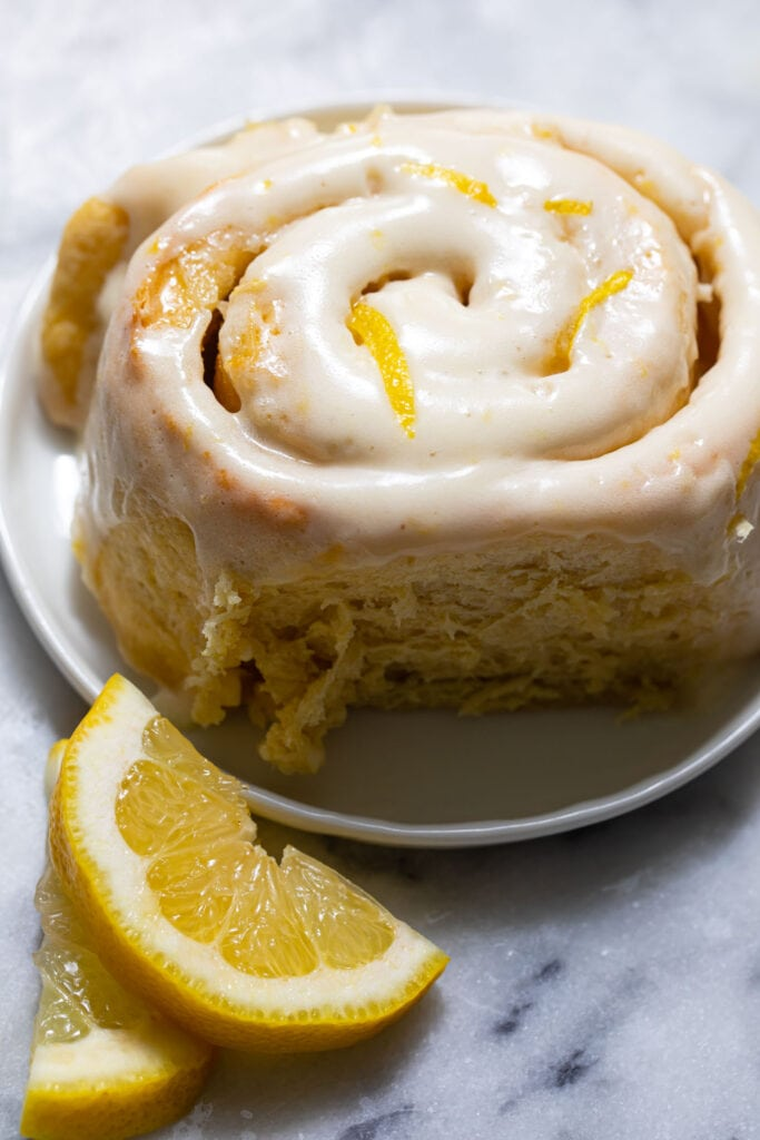 one lemon sweet roll on small white plate with lemon slices on the side