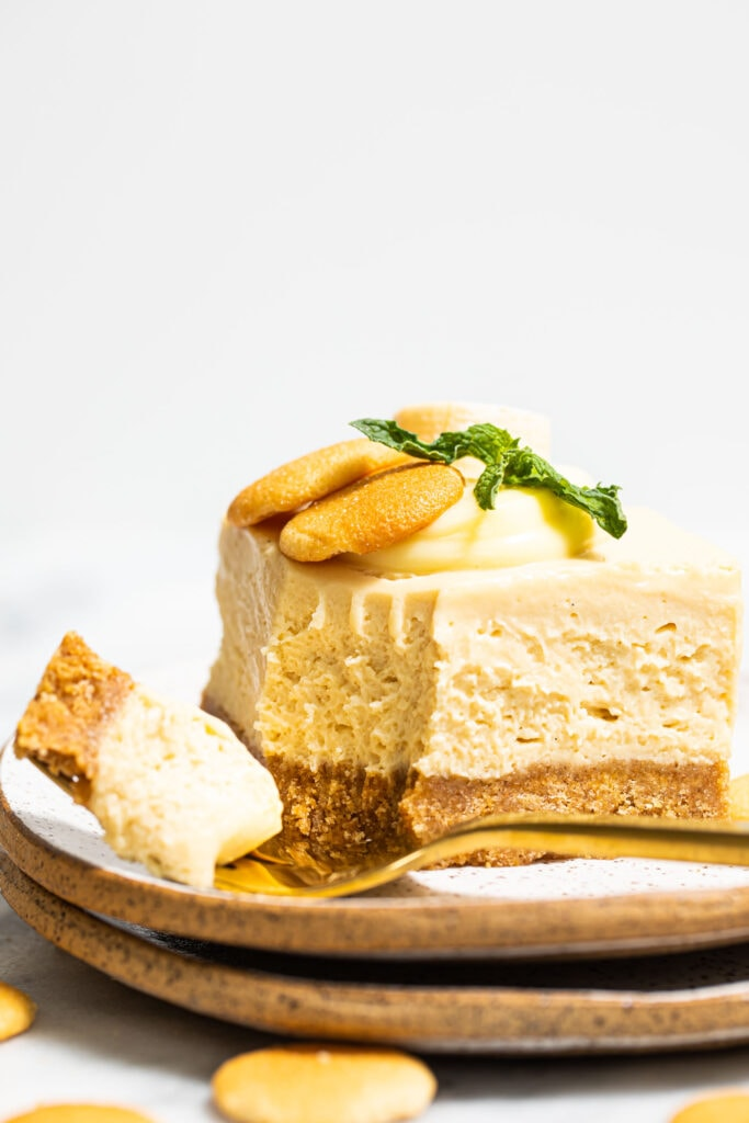 banana pudding cheesecake bar on small speckled plate with gold fork