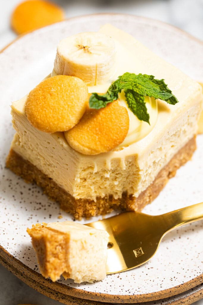 banana pudding cheesecake bar on speckled plate with gold fork