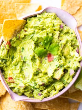 guacamole in pink bowl with tortilla chips around it