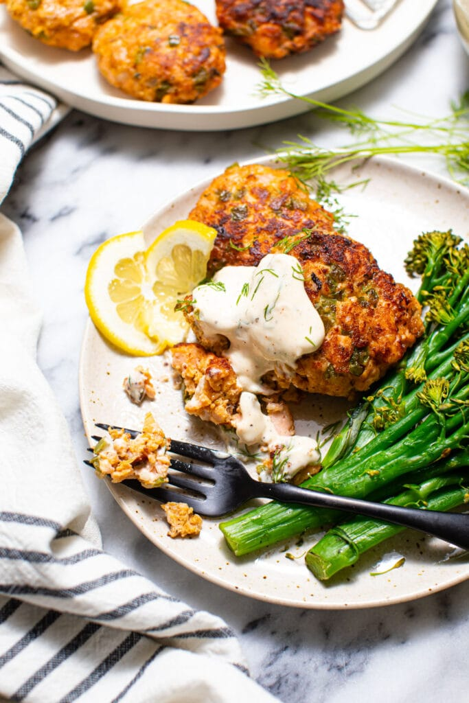 salmon cakes with broccolini and black fork on speckled plate