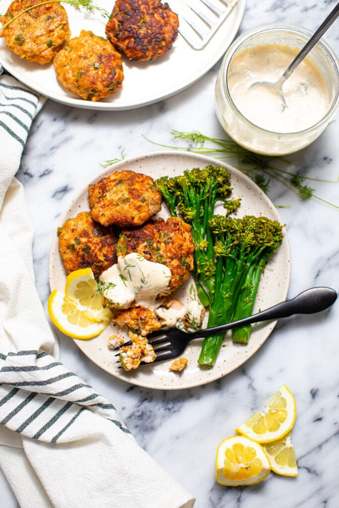 salmon cakes with broccolini on speckled plate with striped linen