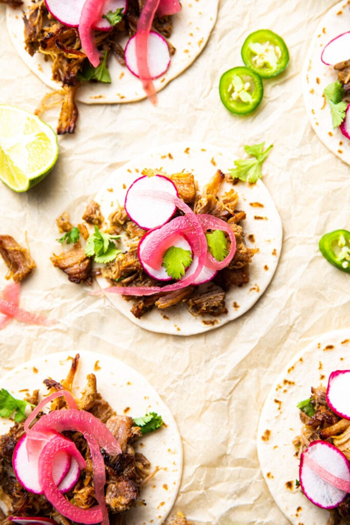 instant pot pork carnitas on top of tortillas with pickled red onions