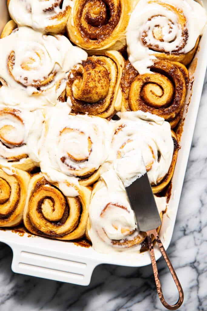 half iced peach cobbler cinnamon rolls with icing knife in white baking dish