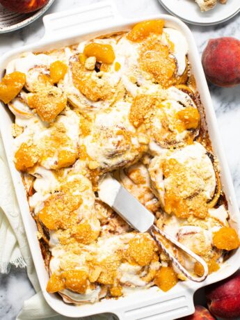 peach cobbler cinnamon rolls in white baking dish on marbled surface