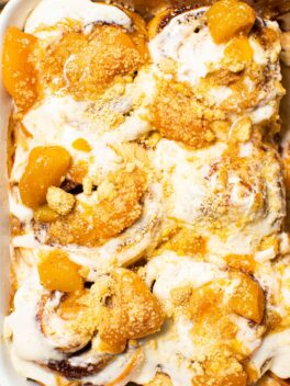 peach cobbler cinnamon rolls with bits of peaches and crushed cookies on top
