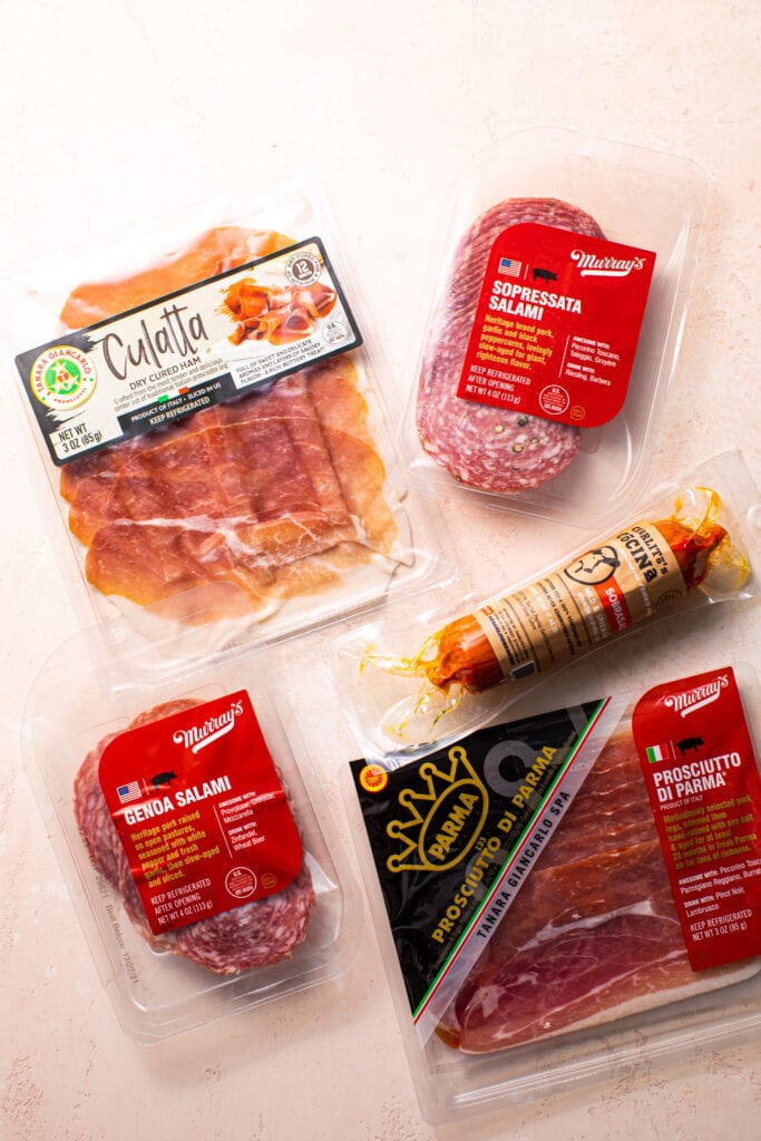 different types of meat for charcuterie board on pink surface