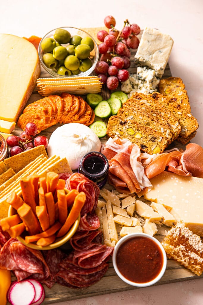 side of charcuterie board filled with cheese, meat, and vegetables