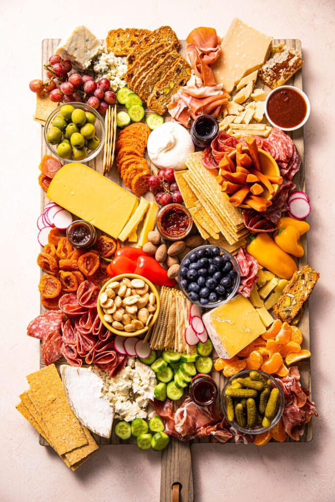 charcuterie board filled with meat, cheese, and fruit on wooden board