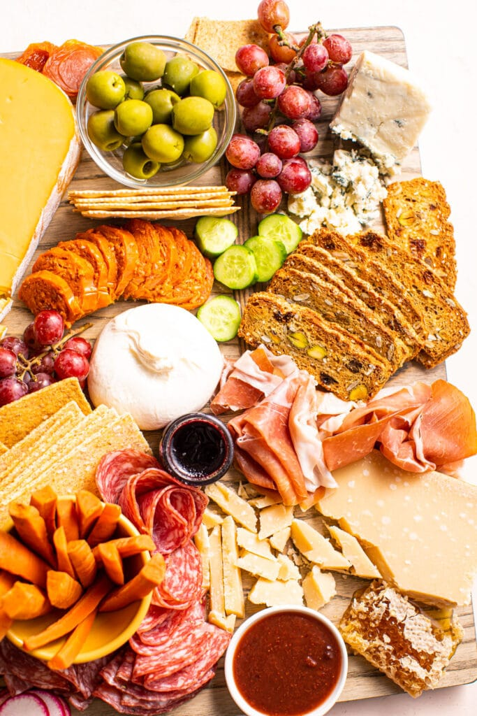crackers, cheese, fruit, and meat on charcuterie board