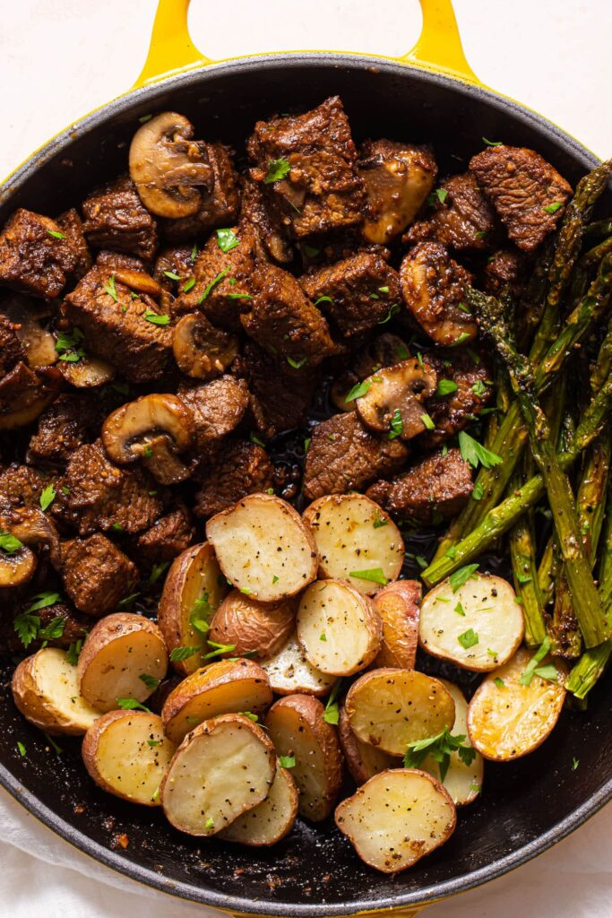 close up of steak tips and roasted potatoes and asparagus in yellow skillet