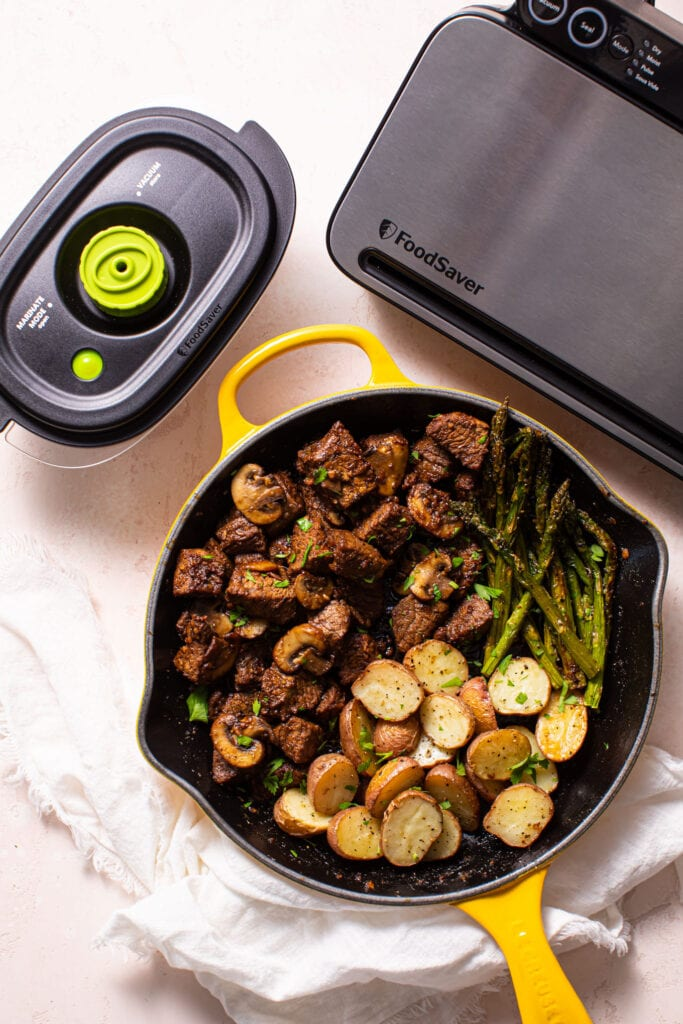 steak tips with roasted potatoes and asparagus in yellow skillet and food saver preservation system