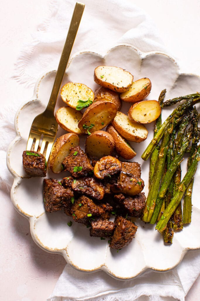 steak tips with roasted potatoes and asparagus on white scalloped plate