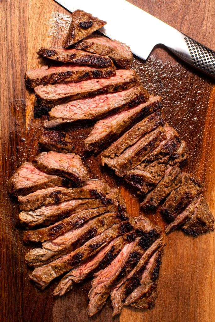 sliced steak on wood cutting board