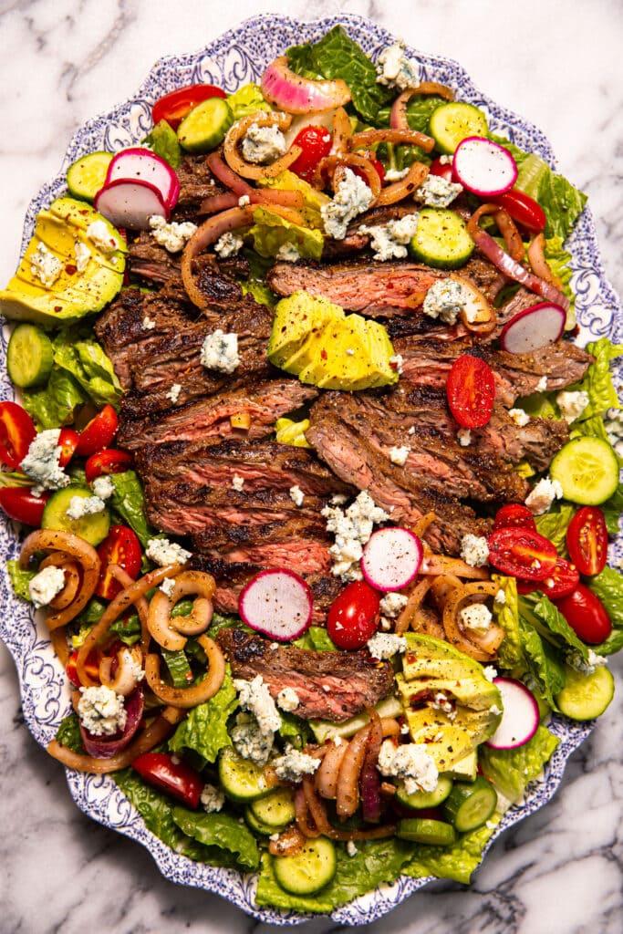 loaded steak salad on antique blue and white platter