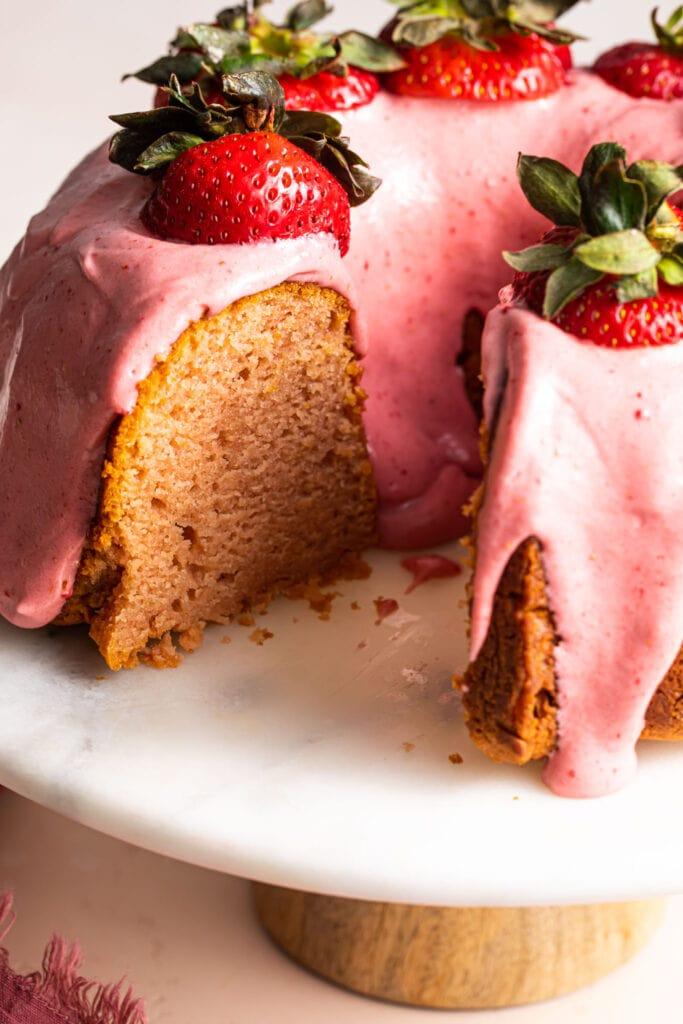 strawberry bundt cake with icing on cake platter