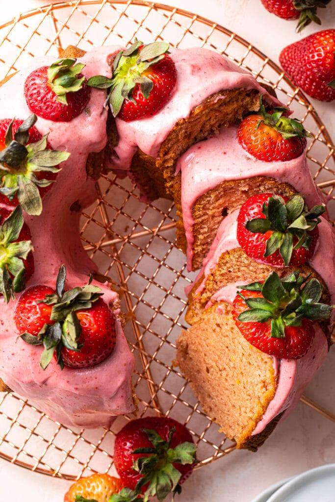 sliced strawberry bundt cake on copper wire rack