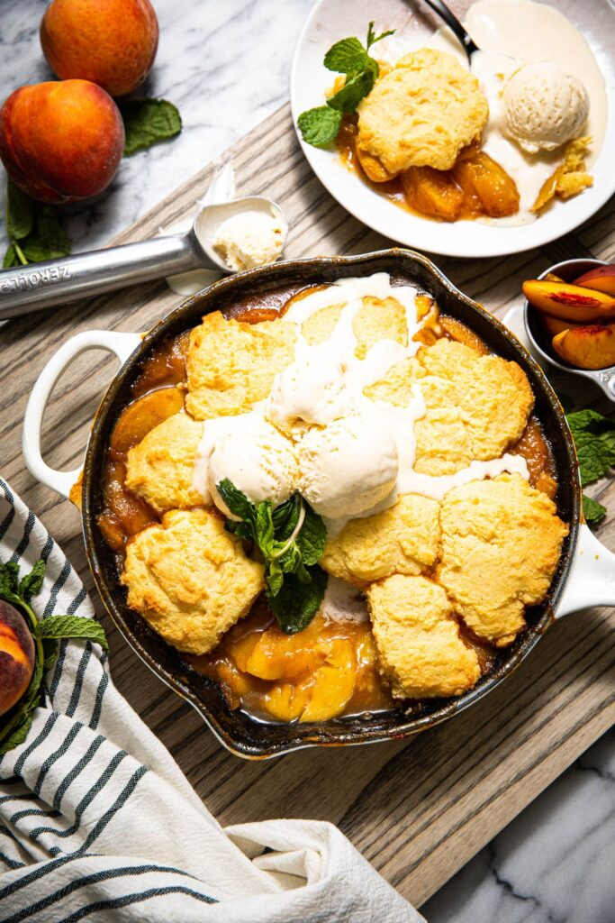skillet peach cobbler on wood board with striped linen