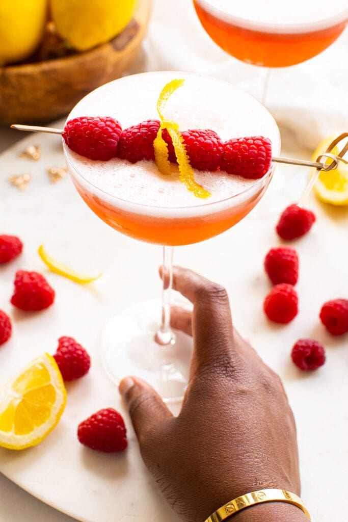black hand holding clover club cocktail on white marble platter