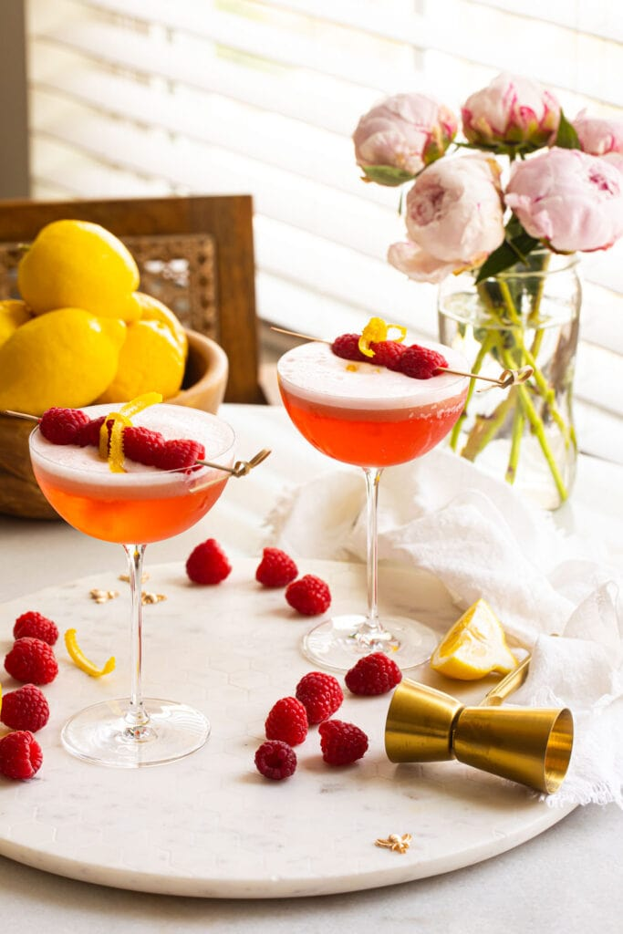 two clover club cocktails with raspberries on white marble platter with flowers