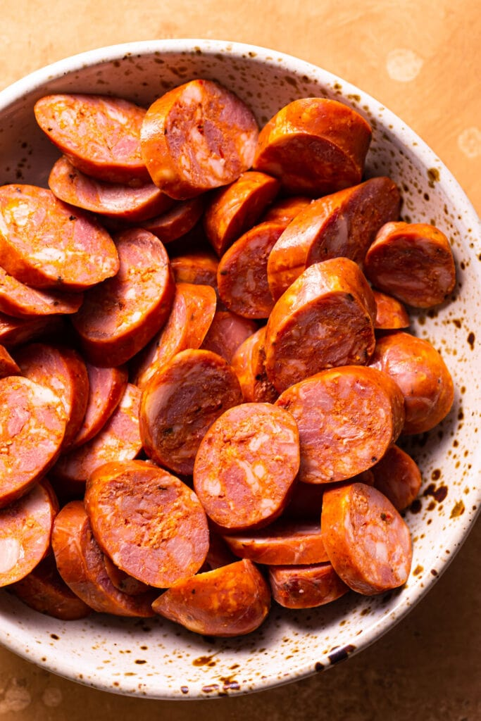 uncooked sausage rounds in speckled bowl