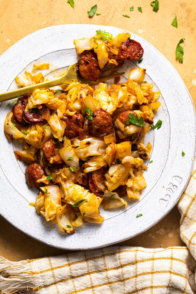 cabbage and sausage on white plate with gold fork