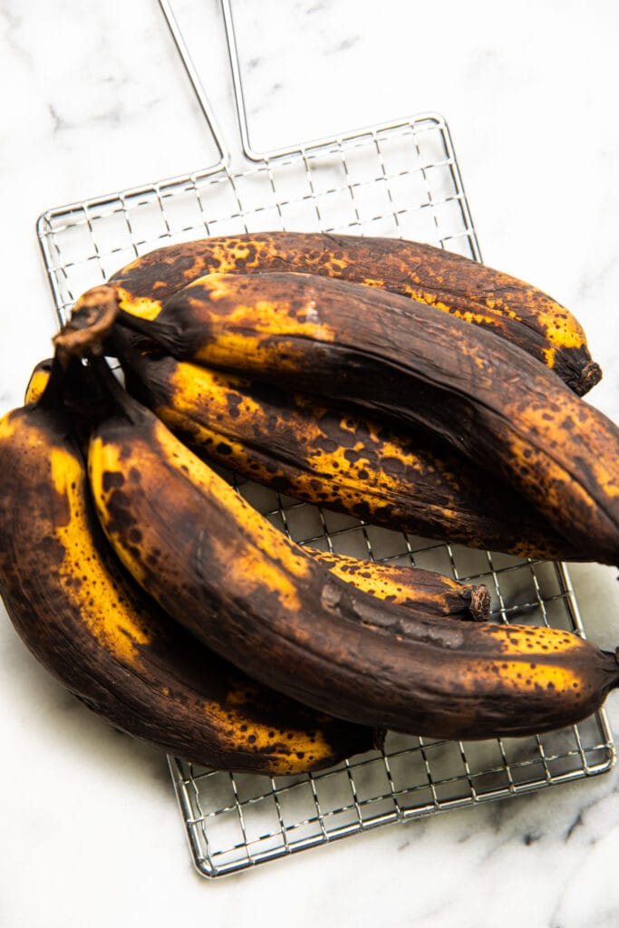 super ripe bananas on top of wire rack on marbled surface