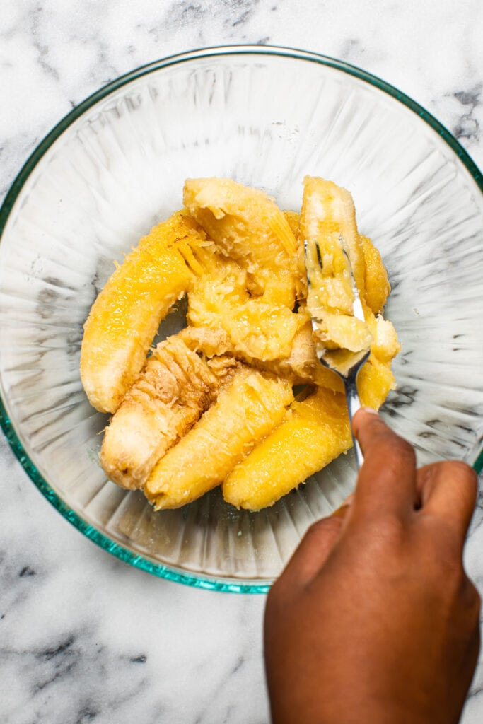 black hand mashing ripe bananas in glass bowl