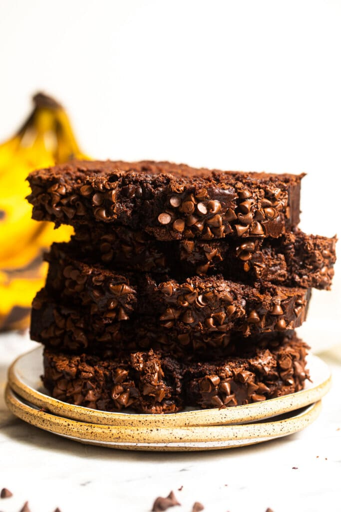 slices of chocolate banana bread stacked on top of each other on small speckled plate