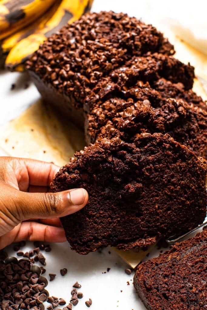 black hand grabbing a slice of chocolate banana bread