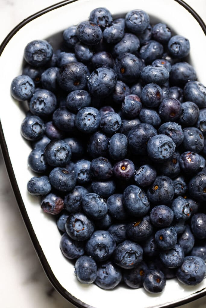 close up of blueberries in small white enamel baking dish