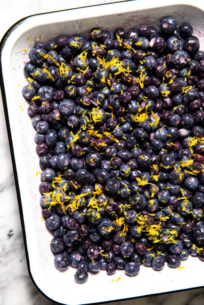blueberry cobbler mixture inside of large white baking dish