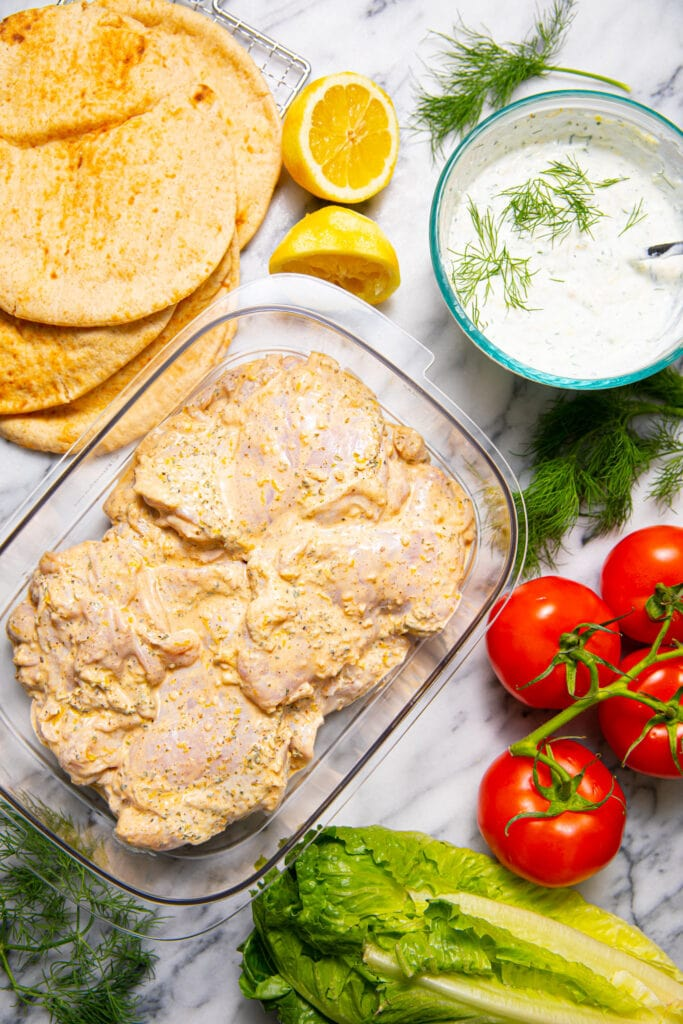 ingredients for greek chicken gyros laid out on marbled surface