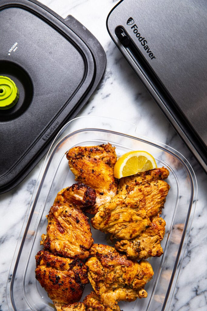 grilled greek chicken in food container on marbled surface