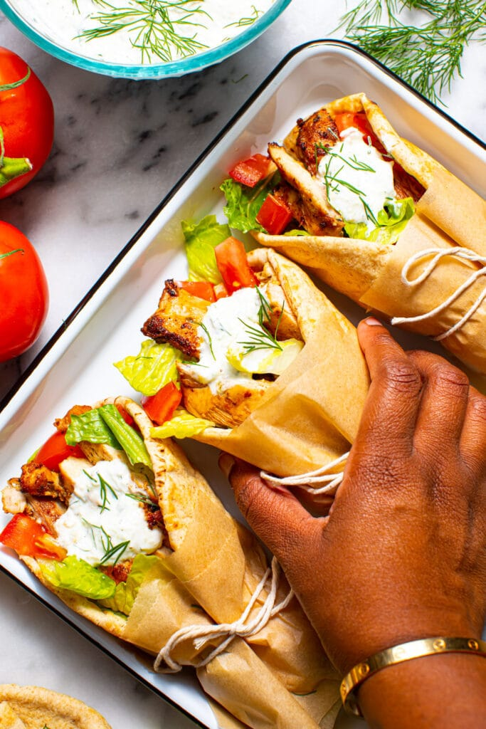 black hand holding greek chicken gyro on small white tray