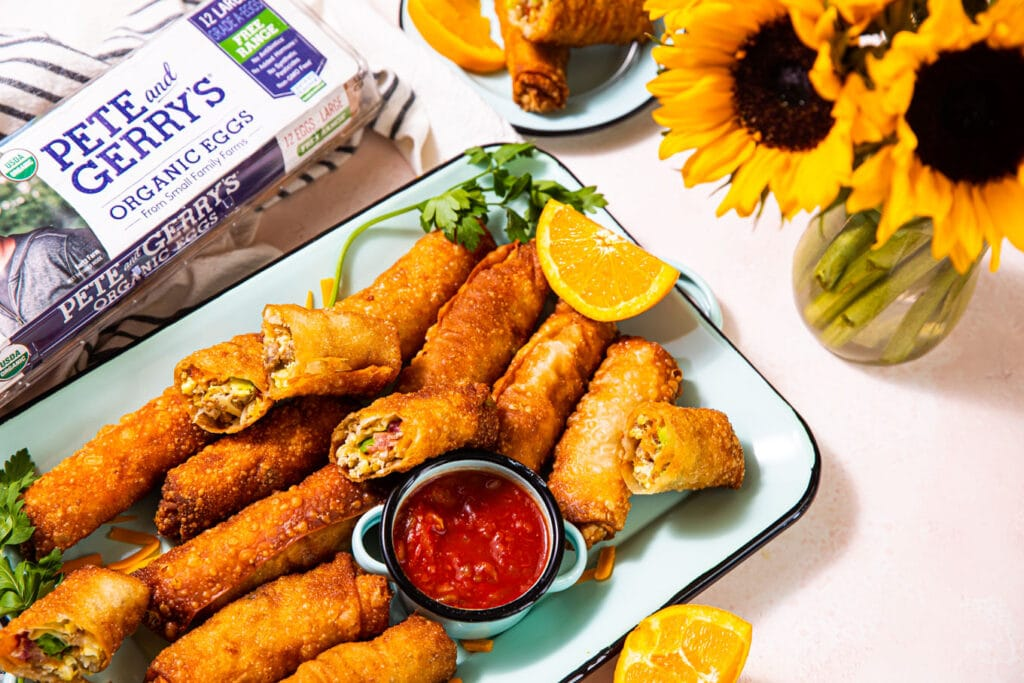 loaded breakfast egg rolls on blue platter with carton of Pete and gerry's eggs