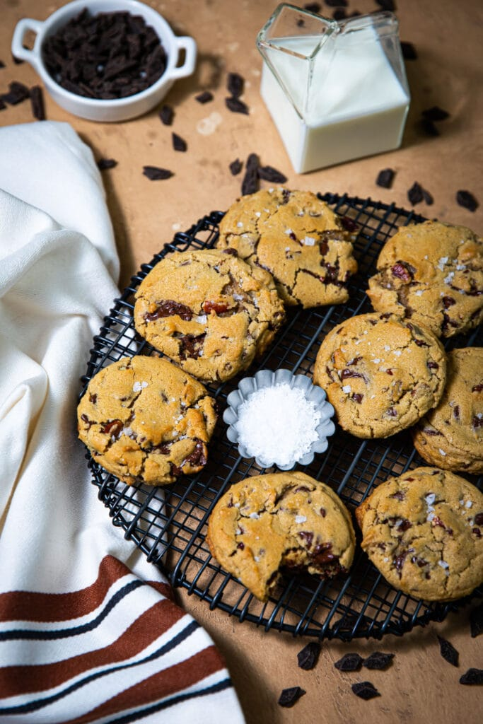 chocolate chunk cookies on black wire rack with striped linen on the side