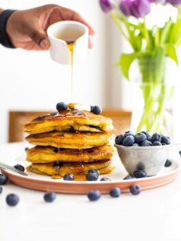 black hand pouring syrup over a stack of fluffy blueberry pancakes