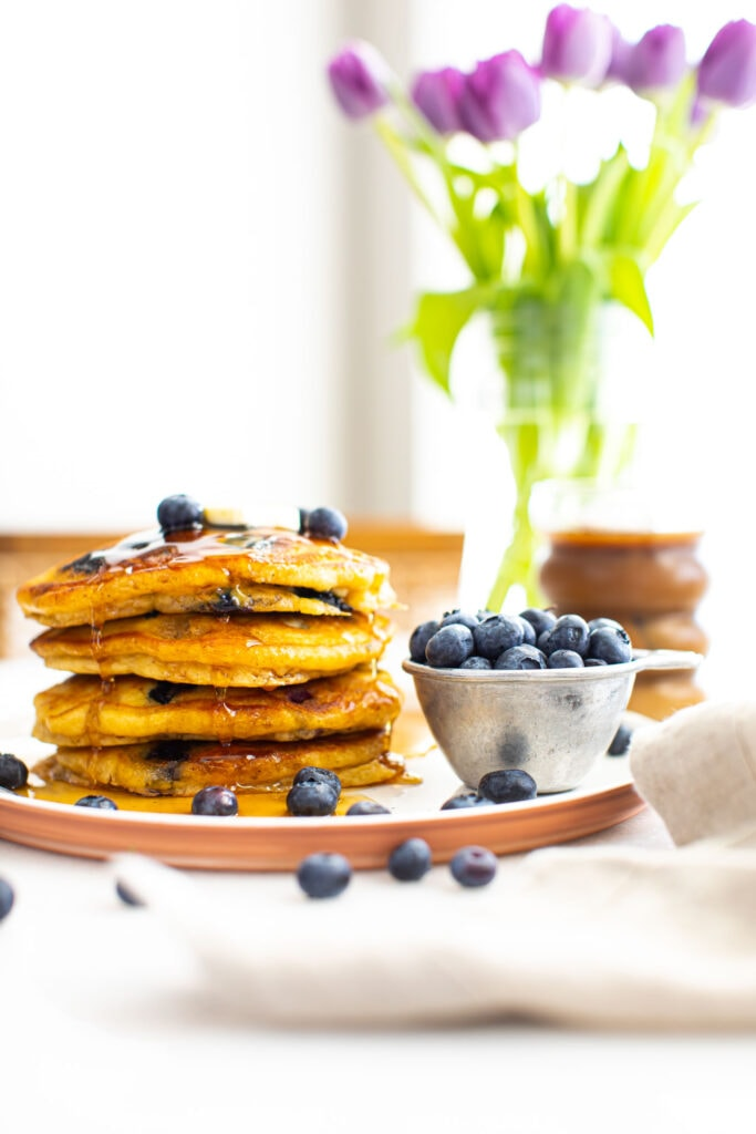 fluffy blueberry pancakes stacked on white plate with flowers in the background