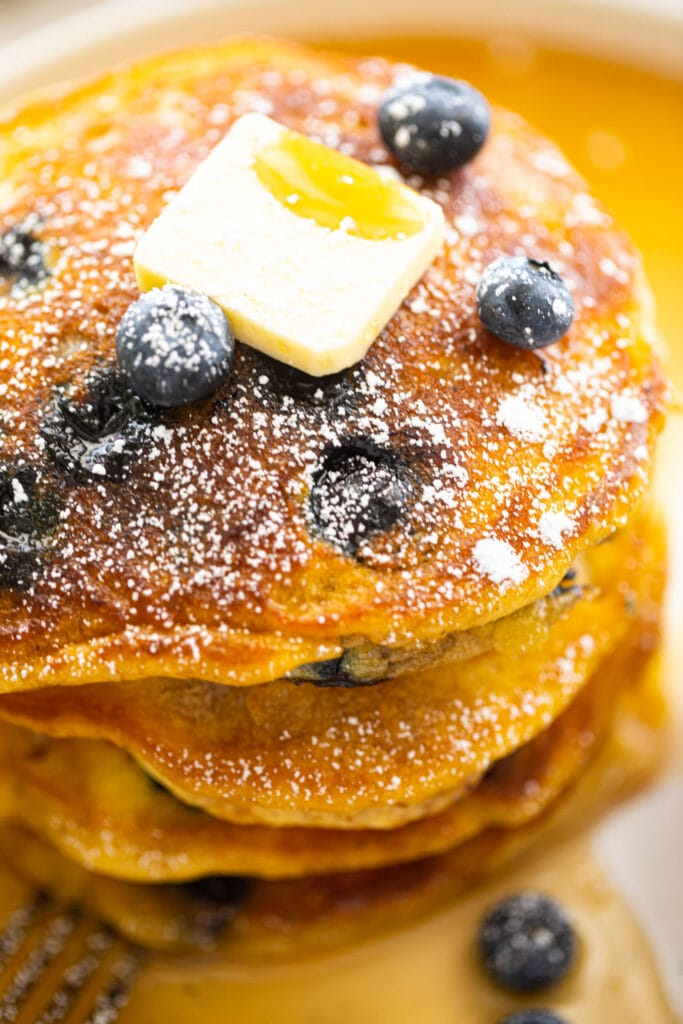 close stack of fluffy blueberry pancakes with butter pat on top