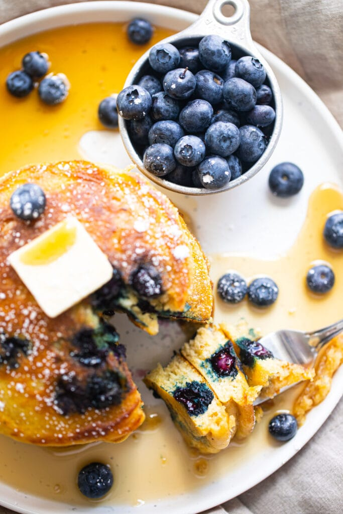 fluffy blueberry pancakes with fresh blueberries on white plate