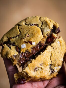 black hand holding chocolate chunk cookie in the air