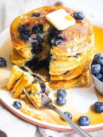 stack of fluffy blueberry pancakes on white plate