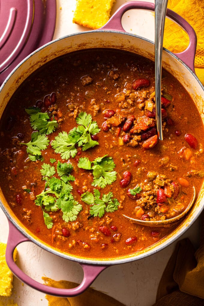 beef chili in large purple pot with silver ladle