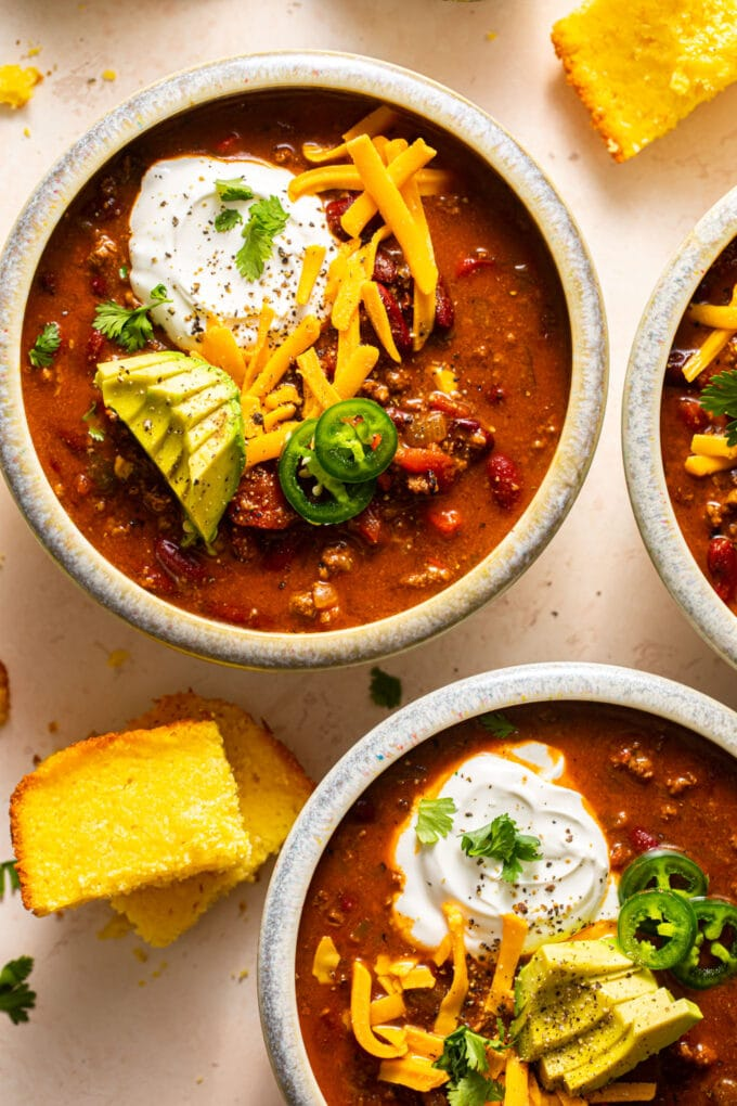 three bowls filled with the best beef chili with toppings on top of chili