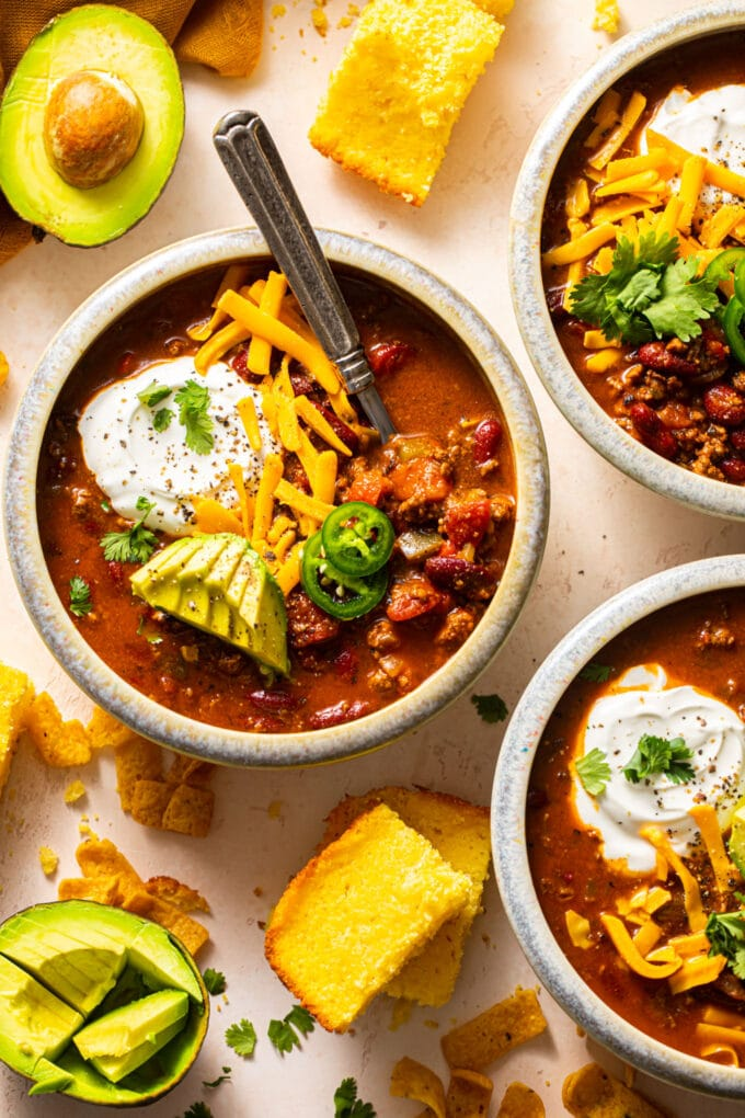 beef chili in small bowls with chopped avocado, sour cream, and shredded cheese on top