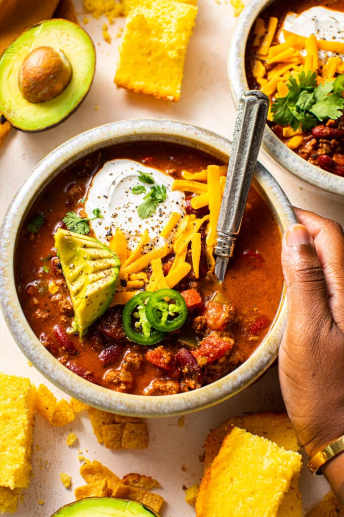 black hand holding a small bowl filled of beef chili