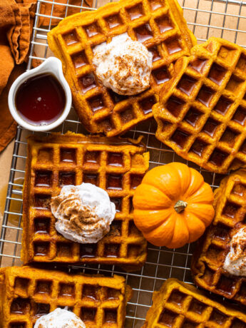pumpkin waffles with whipped cream on silver wire rack